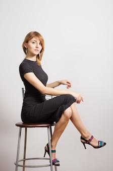 Mädchen im schwarzen kleid sitzt auf einem hohen hocker