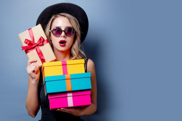 Mädchen im schwarzen kleid und im hut mit geschenkboxen