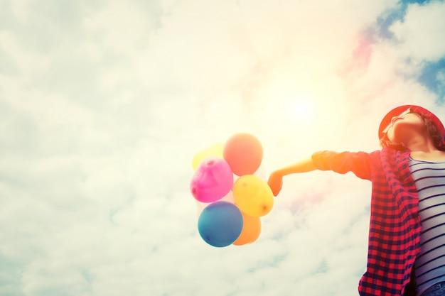 Mädchen im sonnenuntergang mit luftballons