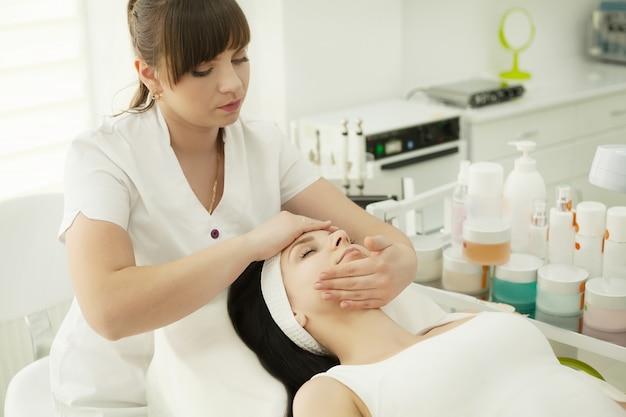 Mädchen im spa-salon. kosmetikerin, die weißes kosmetisches pulver aufträgt