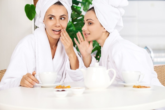 Mädchen im spa. zwei schöne junge frauen im bademantel trinken tee und klatschen beim sitzen vor dem schwimmbad