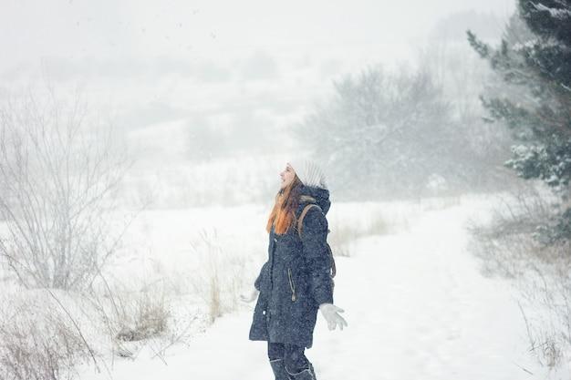 Mädchen im starken schneefall wirft schnee, das mädchen, das spaß in einem harten winter hat
