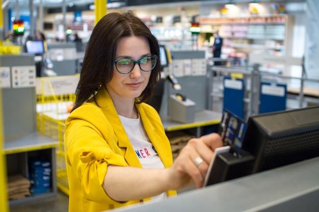 Mädchen im supermarkt, um ihre eigene lesung der kundenkarte zu überprüfen
