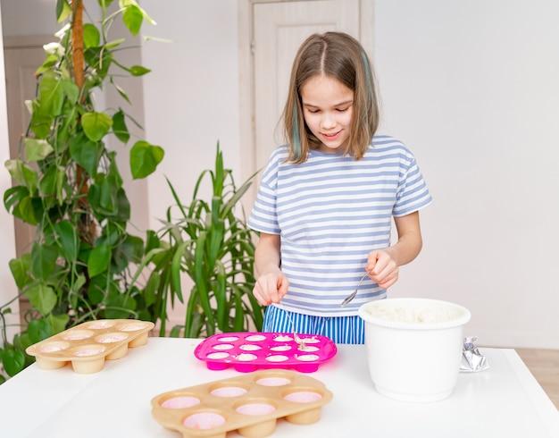 Mädchen im t-shirt legt teig in silikonform für cupcakes. einfache und leckere dessertrezepte