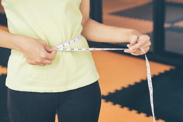 Mädchen im teenageralter benutzen ihre eigenen taillenumfangsriemen. kontrollieren sie sich nach dem training