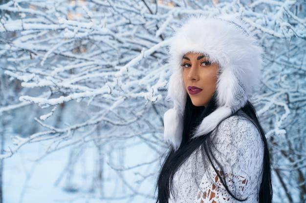 Mädchen im warmen hut auf hintergrund von bäumen mit schnee.
