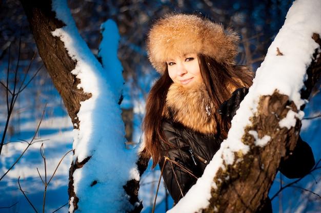 Mädchen im warmen hut mit ohrenklappen auf dem hintergrund der schneedecke