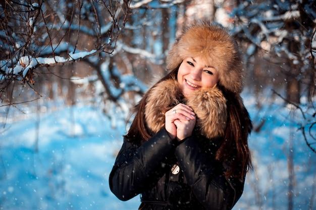 Mädchen im warmen hut mit ohrenklappen auf dem hintergrund des schnees