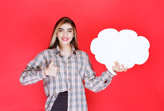 Mädchen im warmen pullover, der ein ideenboard in wolkenform hält und daumen nach oben zeigt