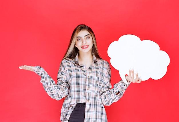 Mädchen im warmen pullover, der ein ideenboard in wolkenform hält und die herausforderung präsentiert