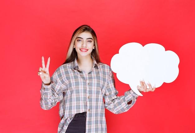 Mädchen im warmen pullover, der ein ideenboard in wolkenform hält und die person vor sich nominiert
