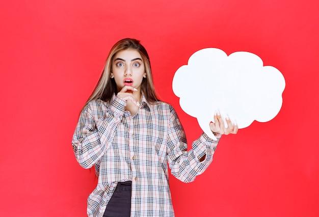 Mädchen im warmen pullover, der ein ideenboard in wolkenform hält und überrascht aussieht