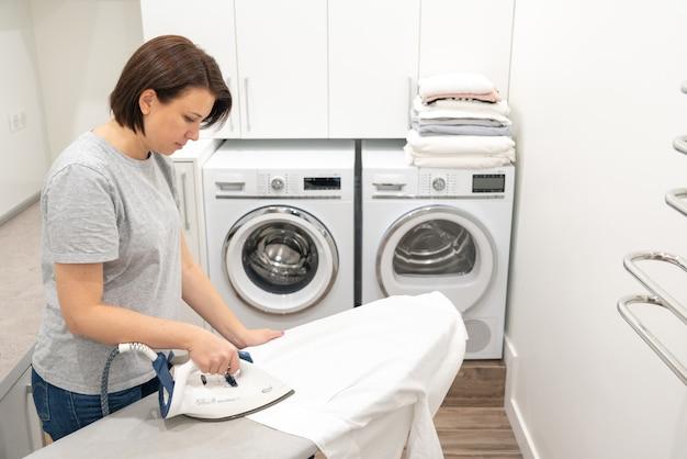 Mädchen im waschraum, der an bord weißes hemd mit waschmaschine bügelt