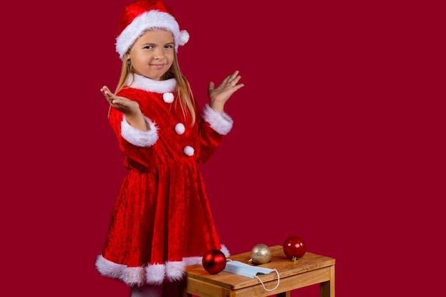 Mädchen im weihnachtsmannkleid mit rotem hut wählt zubehör für weihnachtsbaum im neuen normalen und festlichen tageskonzept.