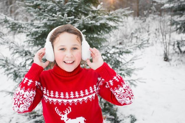 Mädchen im weihnachtspullover und in den ohrenschützern im winterwald