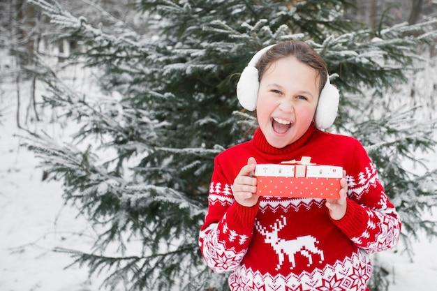 Mädchen im weihnachtspullover und in den ohrenschützern mit geschenk im winterwald