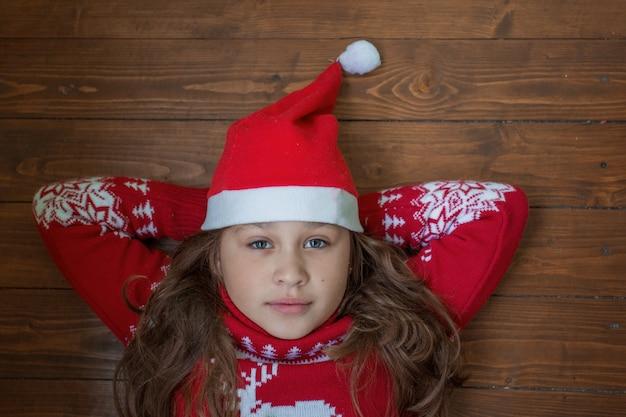 Mädchen im weihnachtspullover und in der weihnachtsmannmütze, die auf dem holzboden liegen.