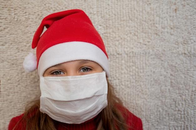 Mädchen im weihnachtspullover und in der weihnachtsmannmütze in der medizinischen maske. hochwertiges foto