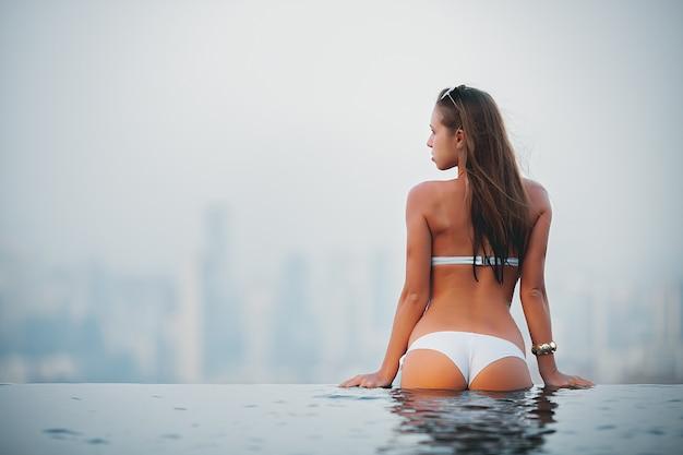 Mädchen im weißen bikini, der am rand des pools auf der oberseite des hotels steht und in einem stadtpanorama schaut