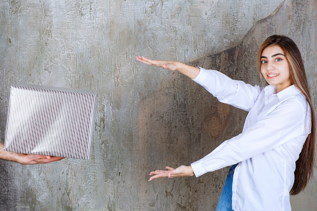 Mädchen im weißen hemd, das auf einer betonmauer steht, wird eine silberne geschenkbox und sehnsüchtige hände angeboten, um sie zu nehmen.