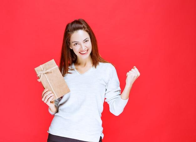 Mädchen im weißen hemd, das eine geschenkbox hält und positives handzeichen zeigt.