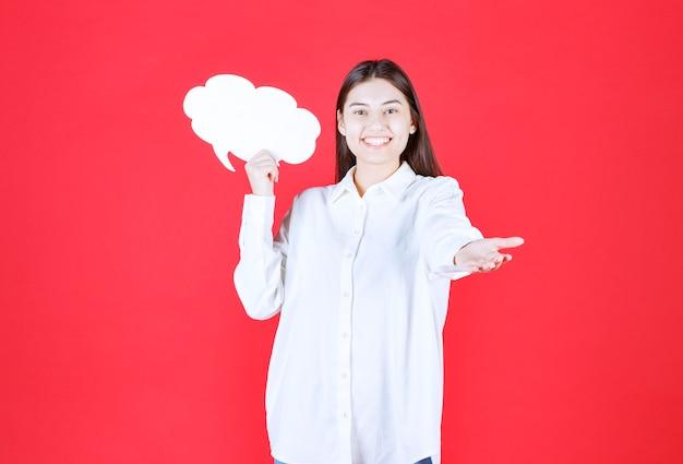 Mädchen im weißen hemd, das eine infotafel in wolkenform hält und jemanden einlädt