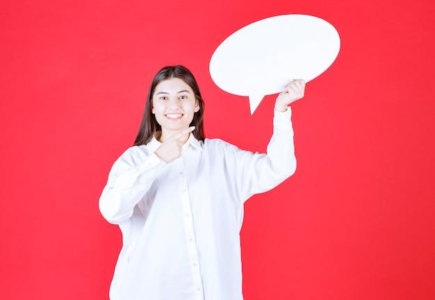 Mädchen im weißen hemd, das eine ovale infotafel hält und verwirrt und nachdenklich aussieht
