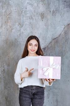 Mädchen im weißen hemd, das eine purpurrote geschenkbox hält.