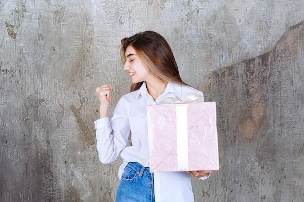 Mädchen im weißen hemd, das eine rosa geschenkbox hält, die mit weißem band umwickelt ist und positives handzeichen zeigt.