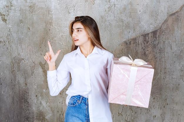Mädchen im weißen hemd, das eine rosa geschenkbox mit weißem band hält und eine gute idee hat.