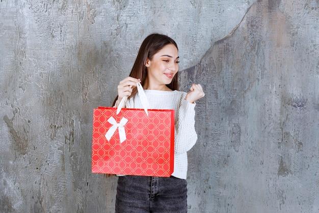 Mädchen im weißen hemd, das eine rote einkaufstasche hält und positives handzeichen zeigt.