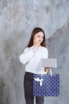 Mädchen im weißen hemd, das eine silberne geschenkbox und eine blaue einkaufstasche hält und jemanden neben ihr anruft, um es zu präsentieren.