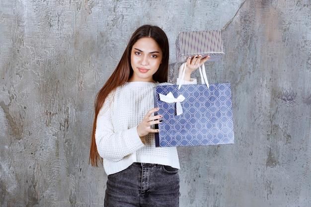 Mädchen im weißen hemd, das eine silberne geschenkbox und eine blaue einkaufstasche hält.