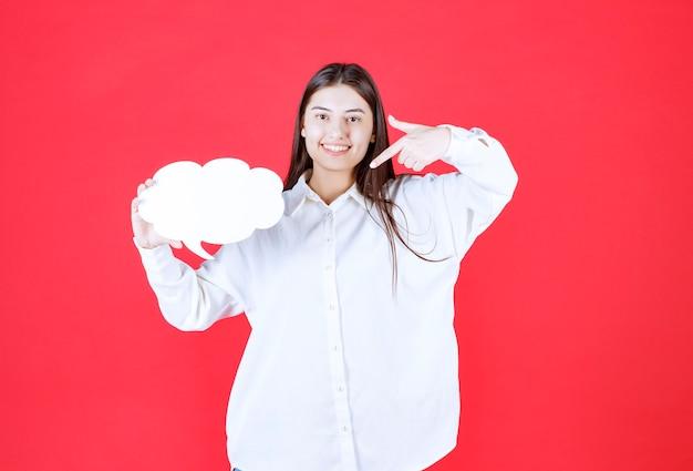 Mädchen im weißen hemd, das eine wolkenform-infotafel hält