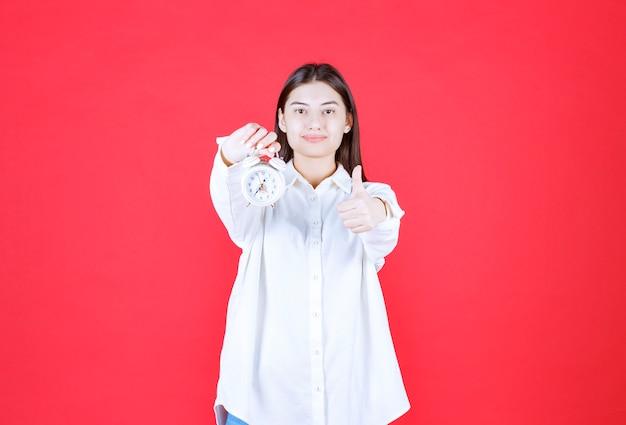 Mädchen im weißen hemd, das einen wecker hält und positives handzeichen zeigt