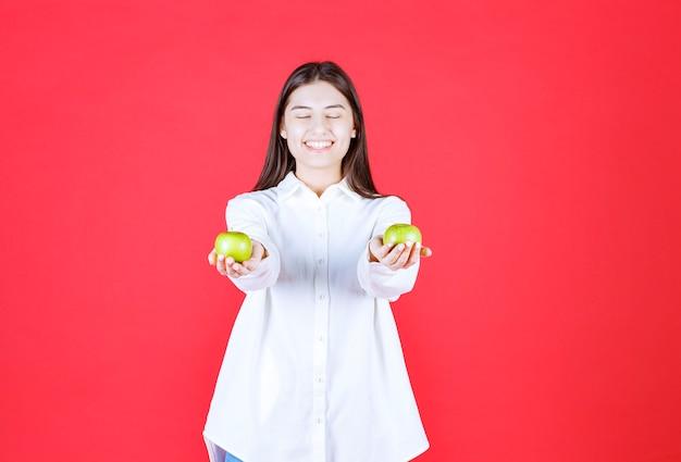 Mädchen im weißen hemd, das grüne äpfel in der hand hält und sie dem kunden anbietet