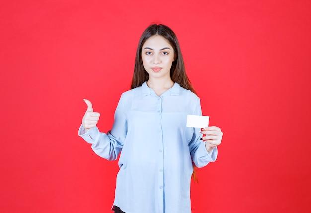 Mädchen im weißen hemd, das ihre visitenkarte darstellt und positives handzeichen zeigt.