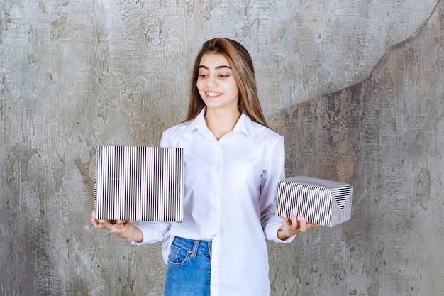 Mädchen im weißen hemd, das silberne geschenkboxen hält.