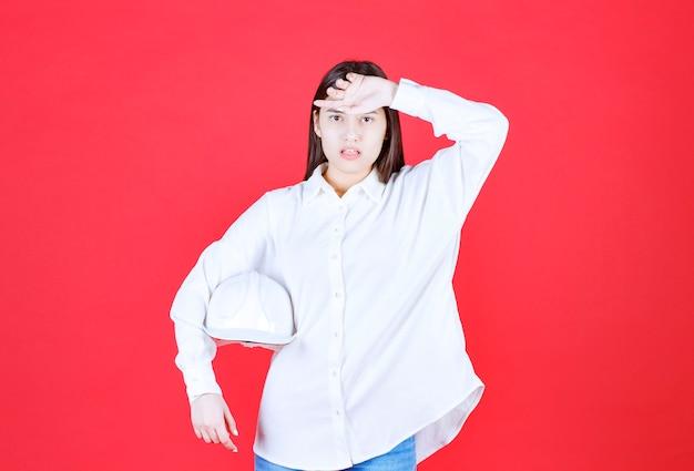 Mädchen im weißen hemd hält einen weißen helm und sieht müde aus