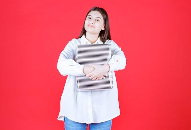 Mädchen im weißen hemd mit einer silbernen geschenkbox