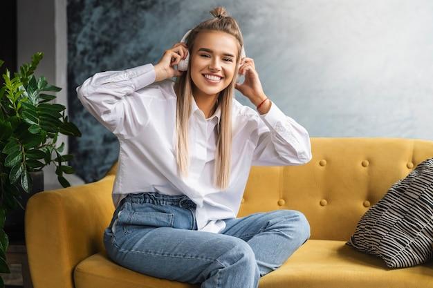 Mädchen im weißen hemd sitzt auf der couch und genießt audio-streaming.