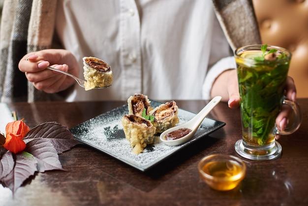 Mädchen im weißen holdinggetränk, das süße sushirolle isst.