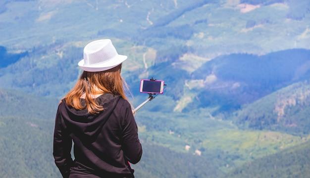 Mädchen im weißen hut oben auf berg macht fotos auf handy