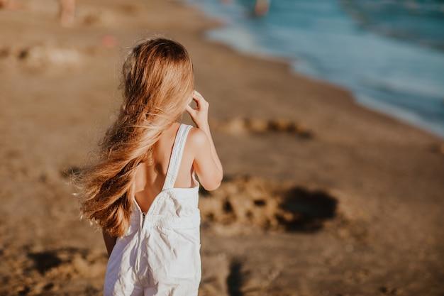 Mädchen im weißen sommeroverall am strand