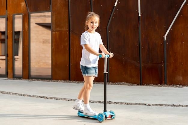 Mädchen im weißen t-shirt, das blauen roller reitet