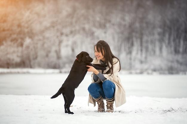 Mädchen im winter, der mit hund spielt