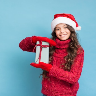 Mädchen im winter kleidet mit einem geschenk in ihren händen