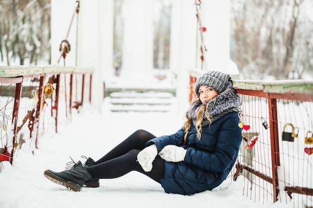 Mädchen im winterpark bedeckt vom schnee