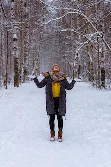 Mädchen im winterpark fängt schneeflocken, die nach oben schauen