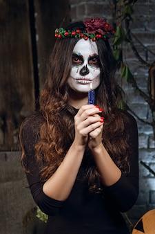 Mädchen im zuckerschädelmake-up, das kerze in ihren armen hält. gesicht malen kunst.